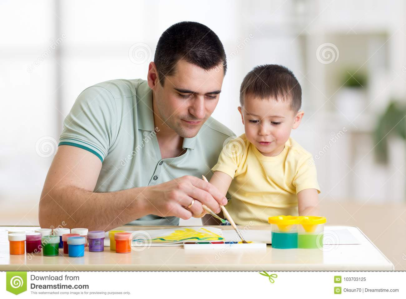 Father and child paint together. Dad teaches son how to paint correct and beautiful on paper. Family creativity and