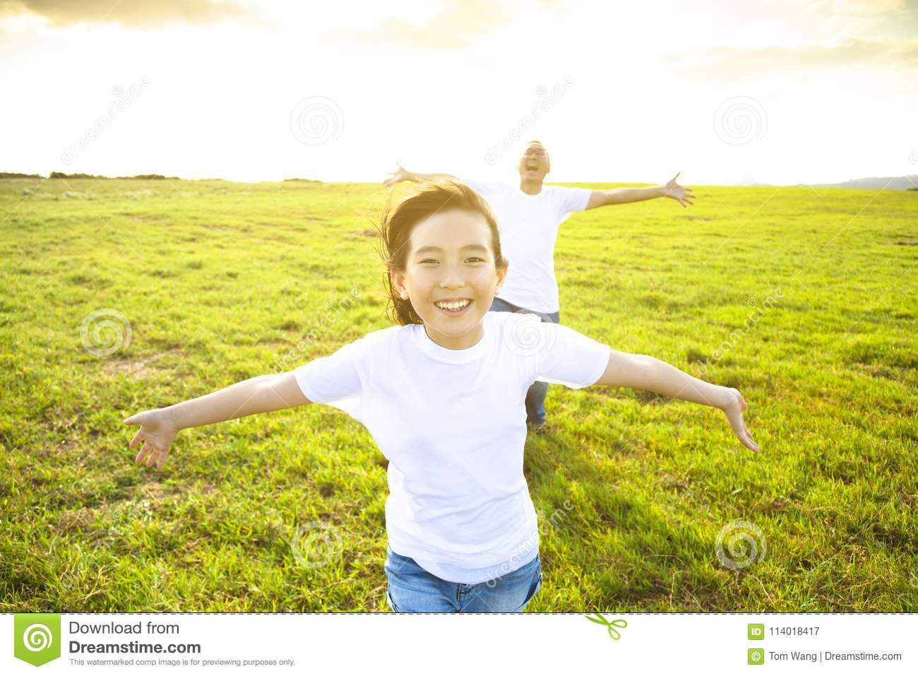 Father and child running on meadow