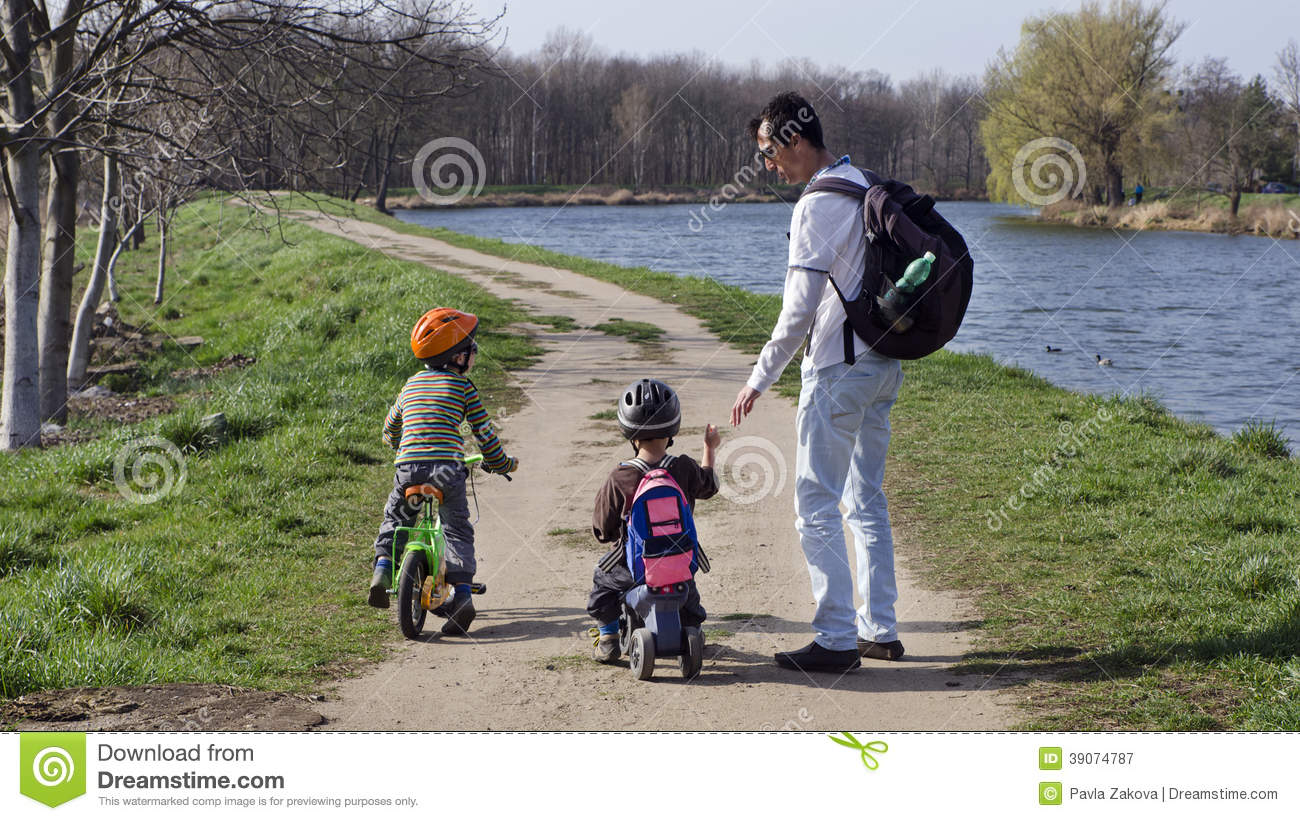 Father and children cycling