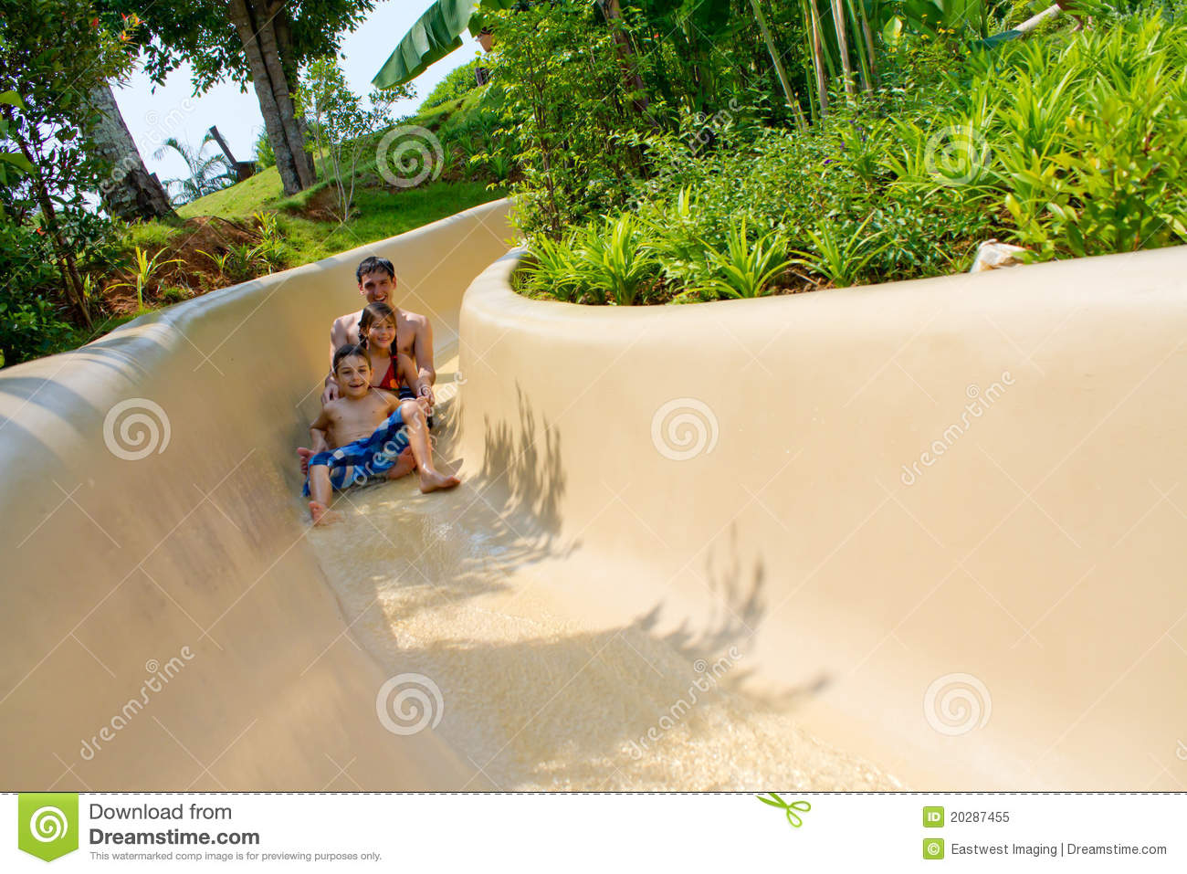 Father And Children Sliding Down Water Slide Stock Image