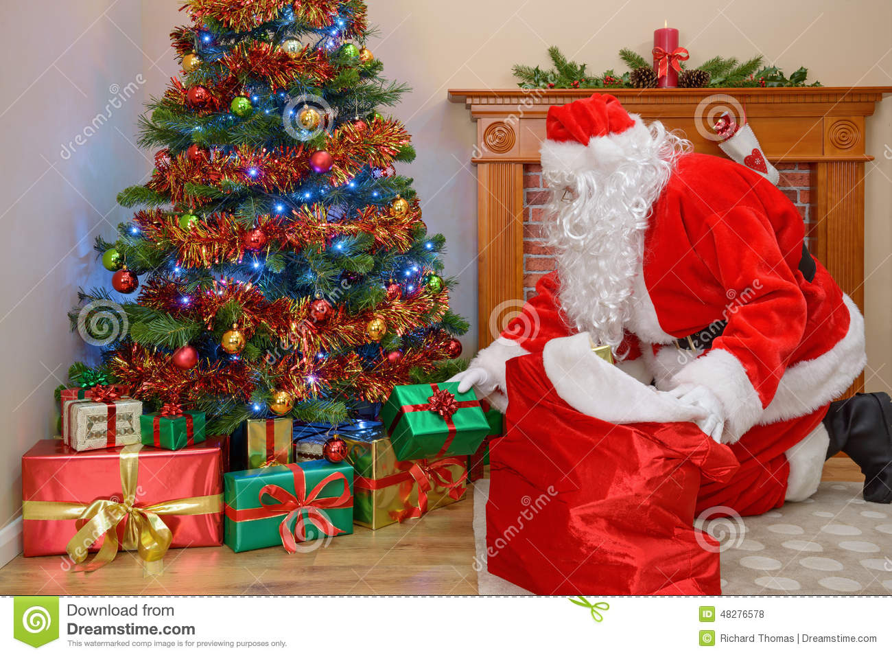 Father Christmas Putting Gifts Under The Tree Stock Photo - Image of ...