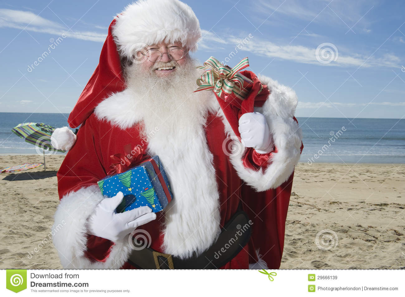 Father Christmas Stands With His Sack On Beach