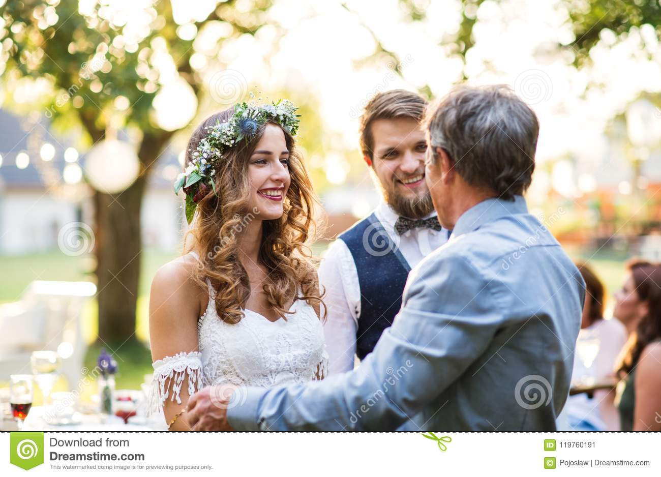 a father congratulating bride and groom at wedding reception in the backyard