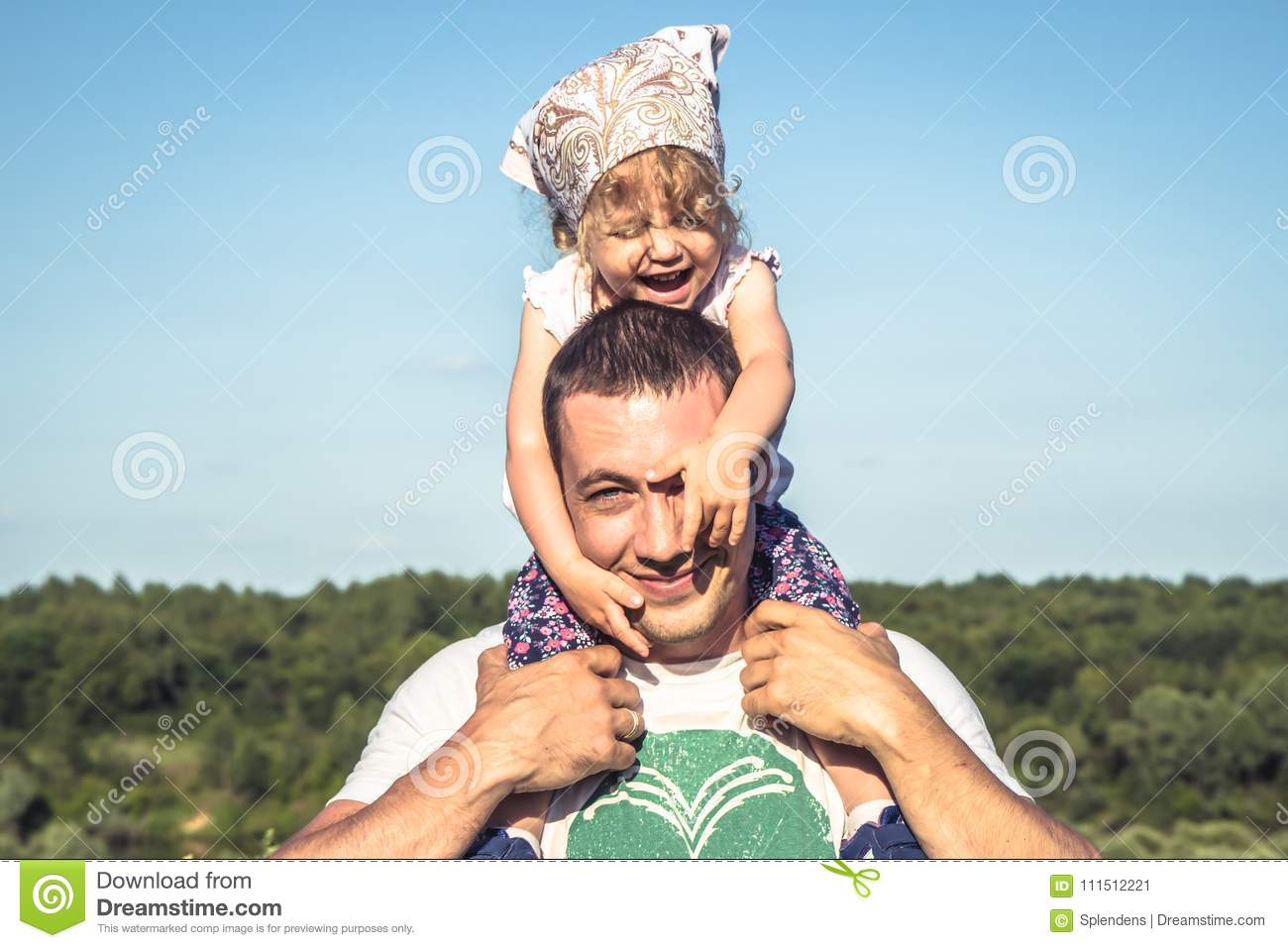 Father cute daughter having fun together as family lifestyle portrait in front of blue sky. Happy father holding his child