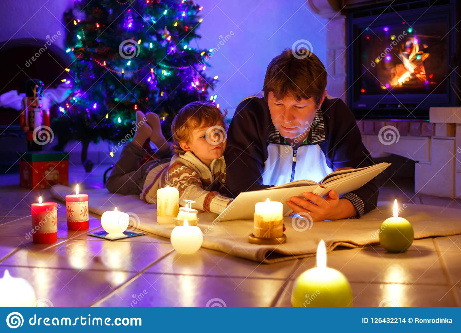 Father and cute little toddler boy reading book by chimney, candles and fireplace.