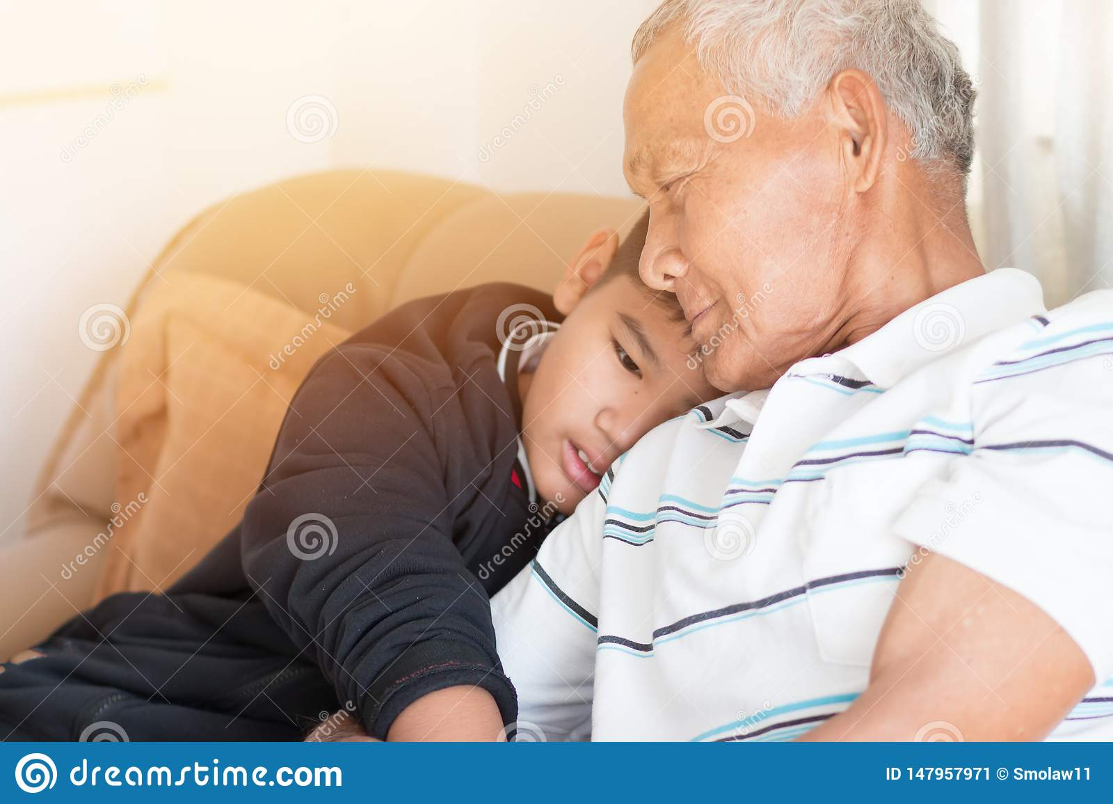 Father and Dad Day concept : Asian retired Grandfather and nephew or grandson, young boy hugging Living in house happily together