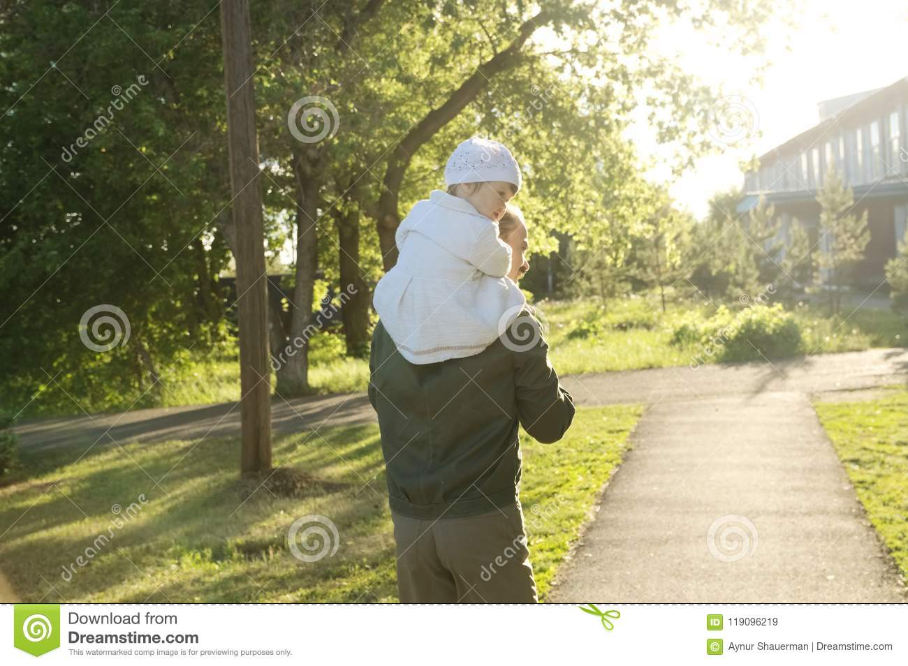 Father with daughter baby on shoulders walking away in park at sunny day. Family lifestyle portrait