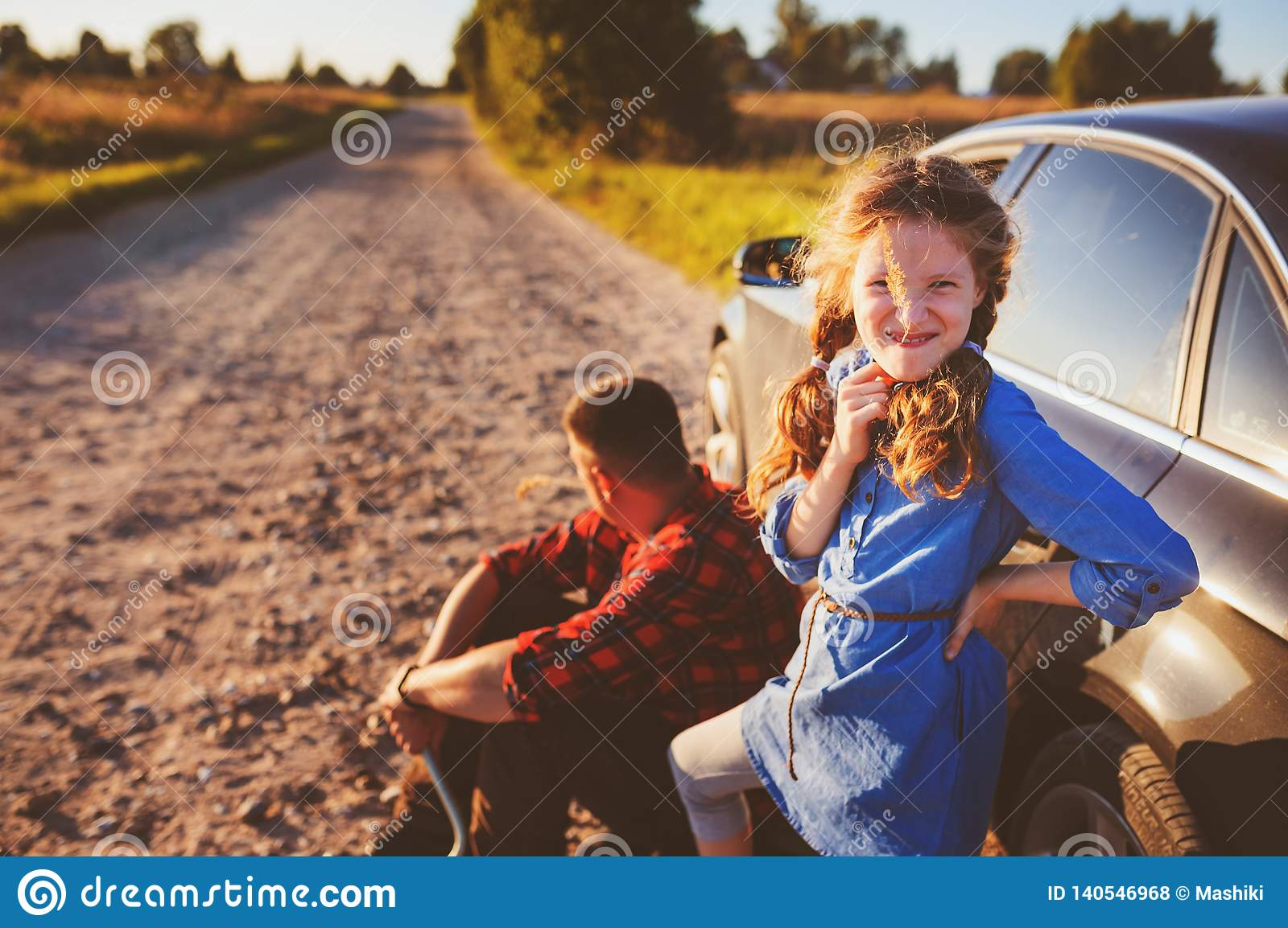 Father and daughter changing broken tire during summer rural road trip.
