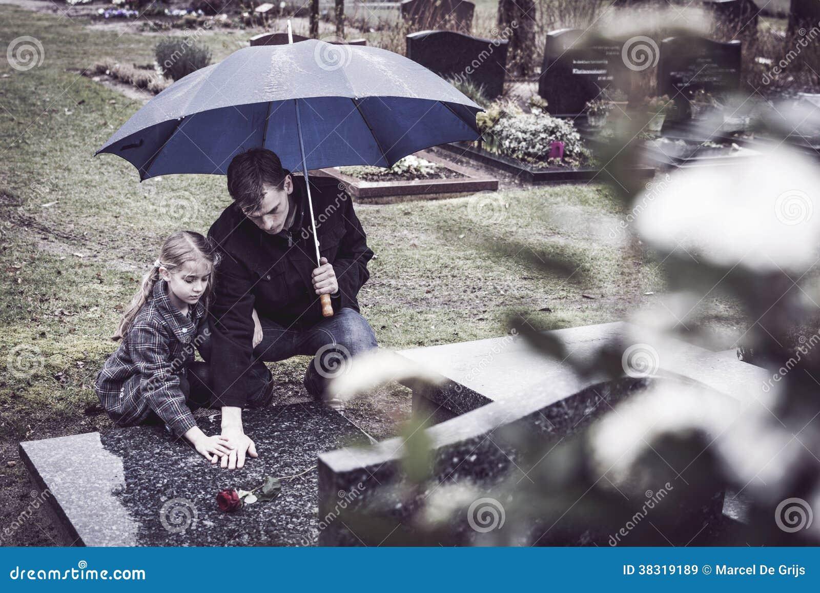 ... kneeling at deceased mothers grave at graveyard. Mourning her death