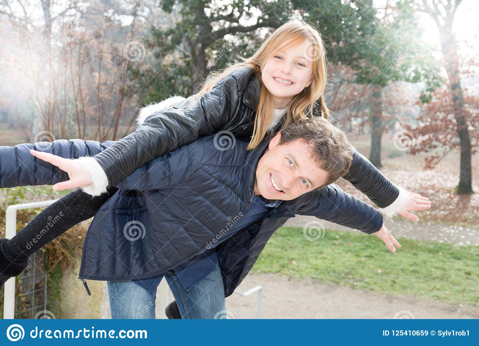 Father and daughter having a fun piggyback in autumn winter park Family