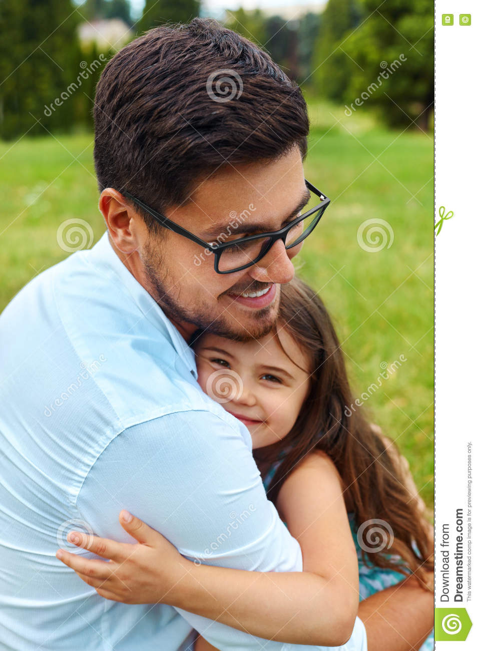 Father And Daughter Hugging In Park. Family Embracing Outdoors