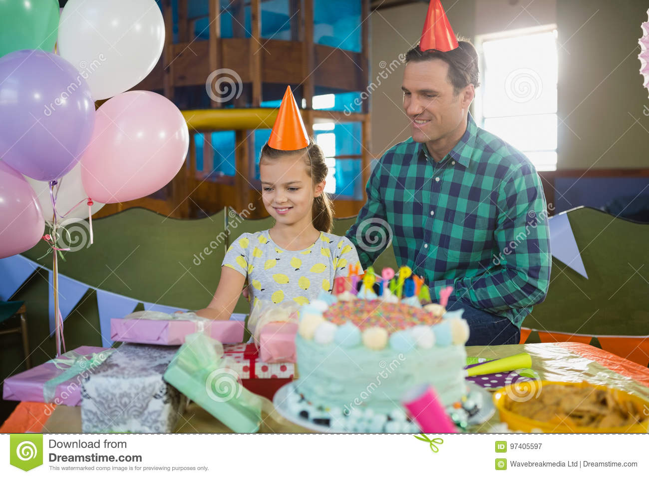 Father And Daughter Looking At Gifts On Table Stock Image
