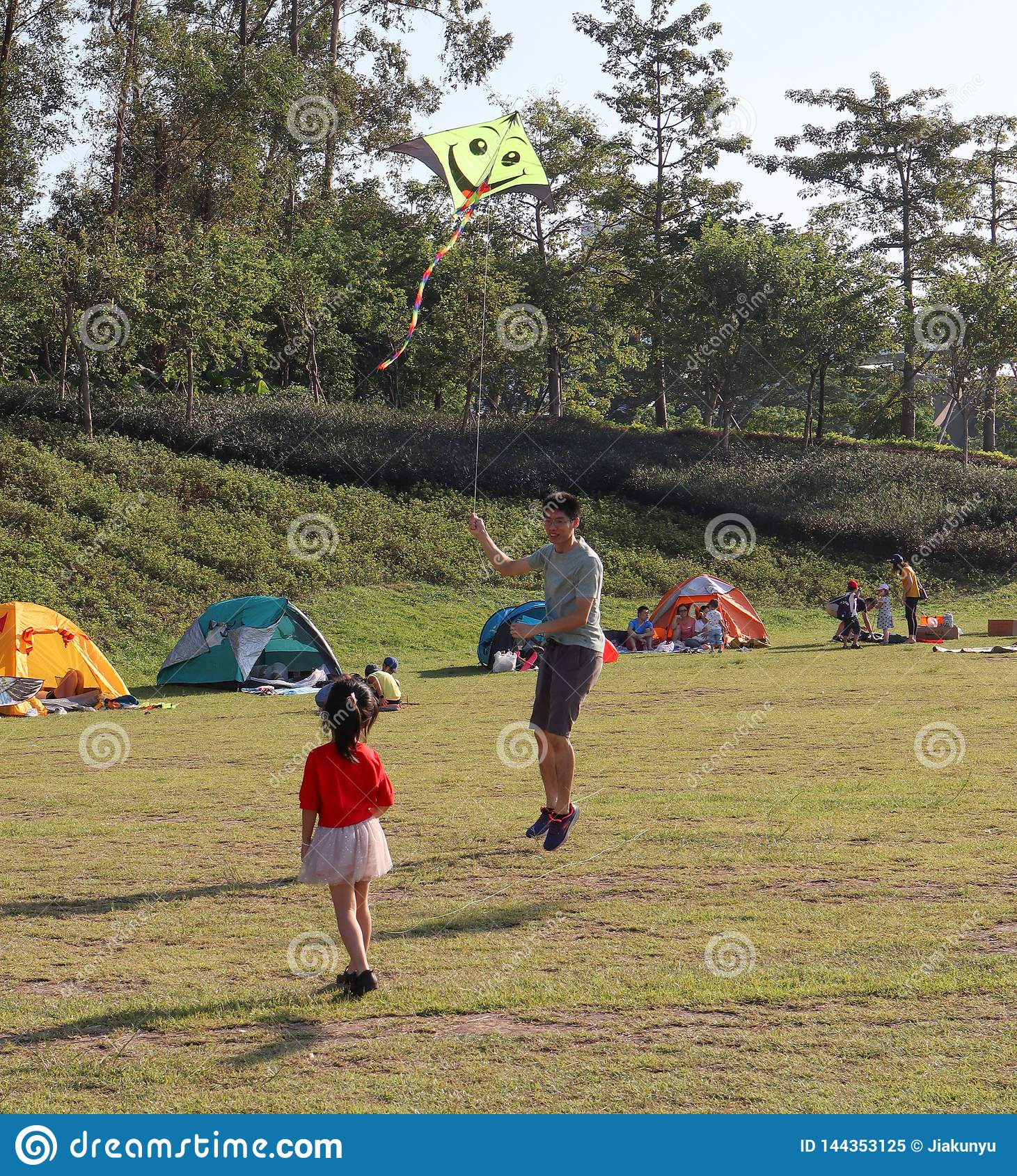 Father and daughter, People camped on the grass in the park, summer in guangzhou, China
