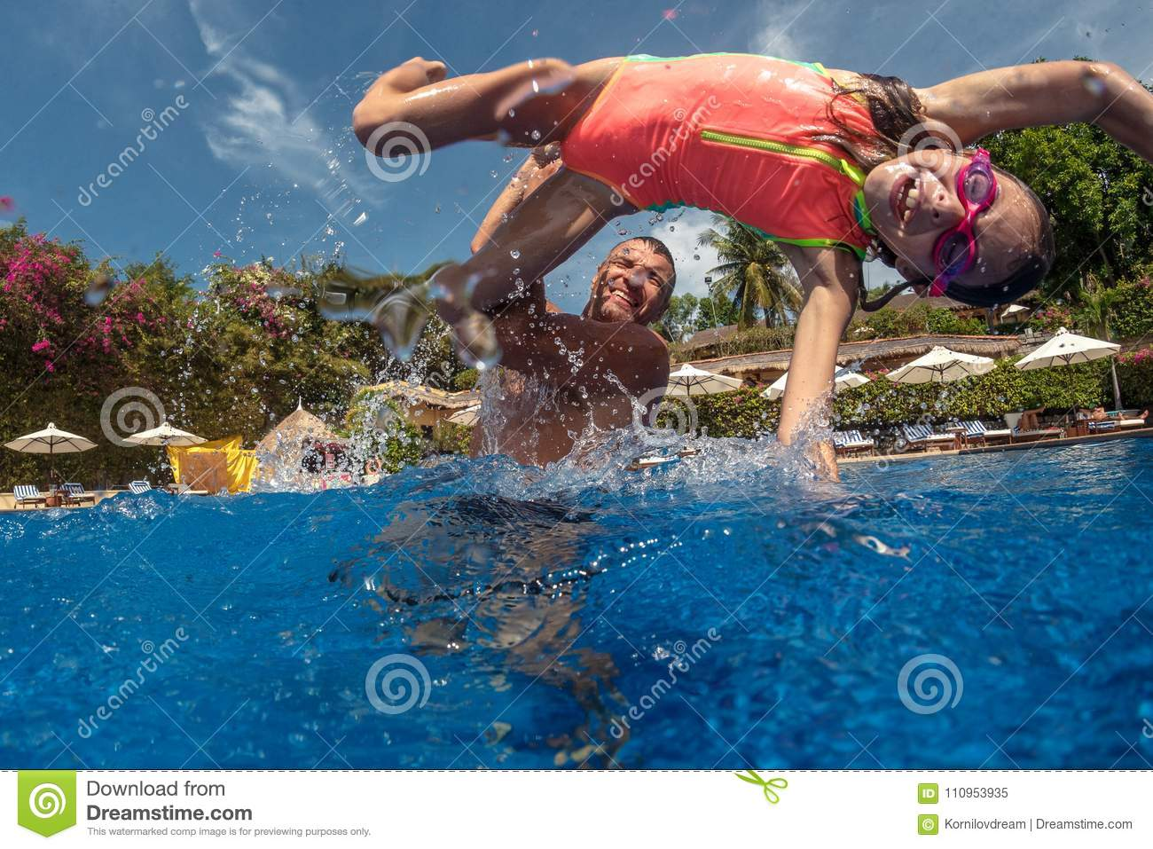 Father and daughter playing in a swimming pool