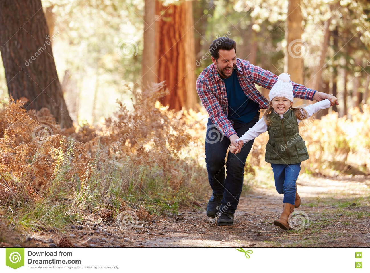 Father And Daughter Running Through Fall Woodland
