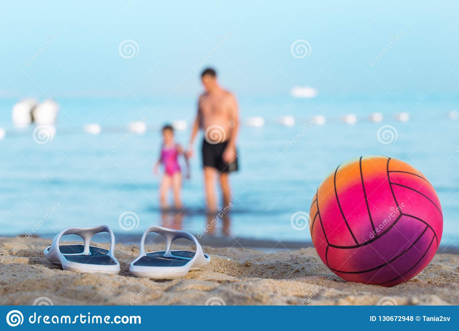 a943115a2937cc Father with daughter coming out of the water on the summer beach blurred  out with flip flops and a beach ball in the foreground