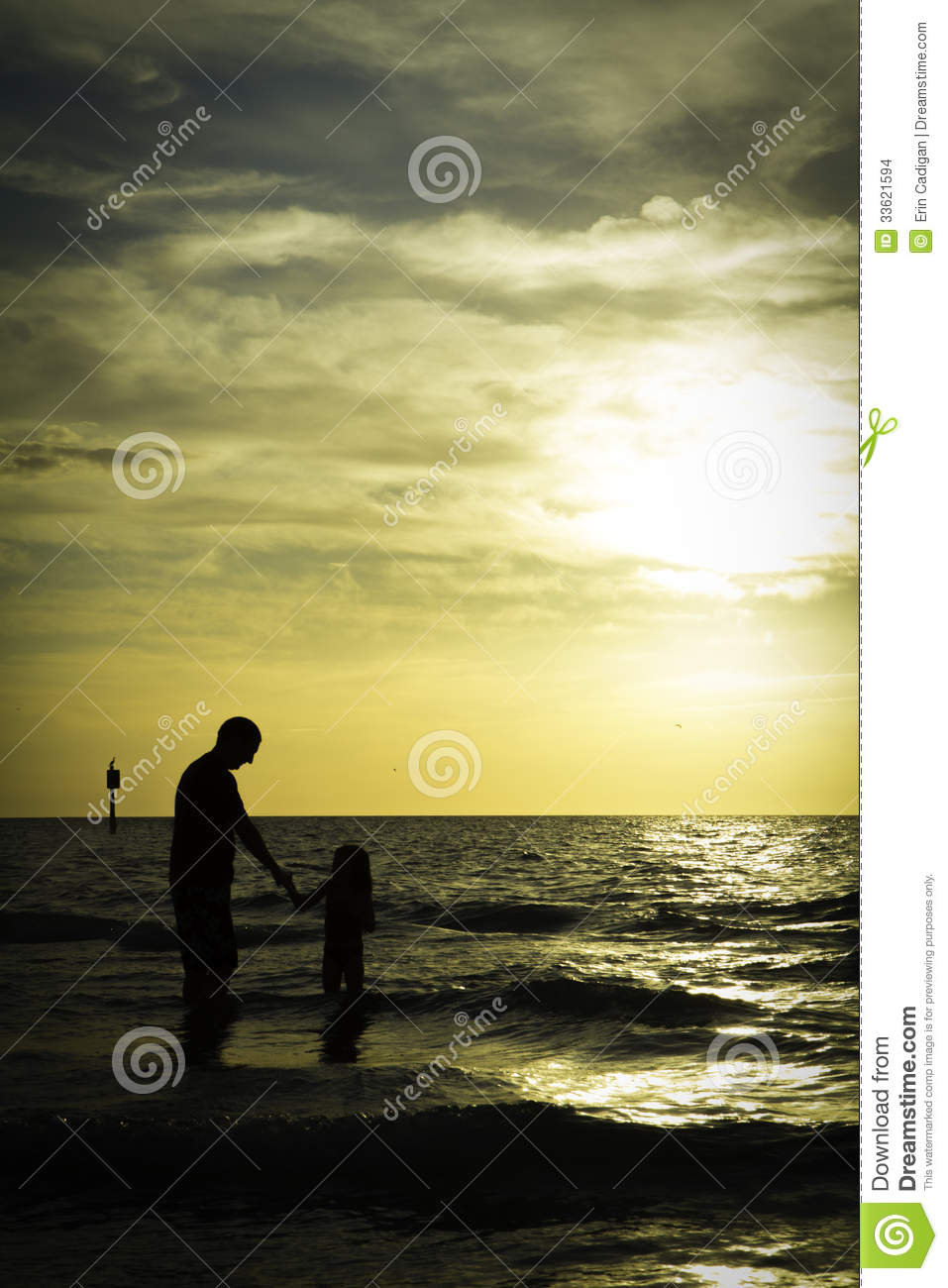 father and daughter sunset silhouettes by the sea stock