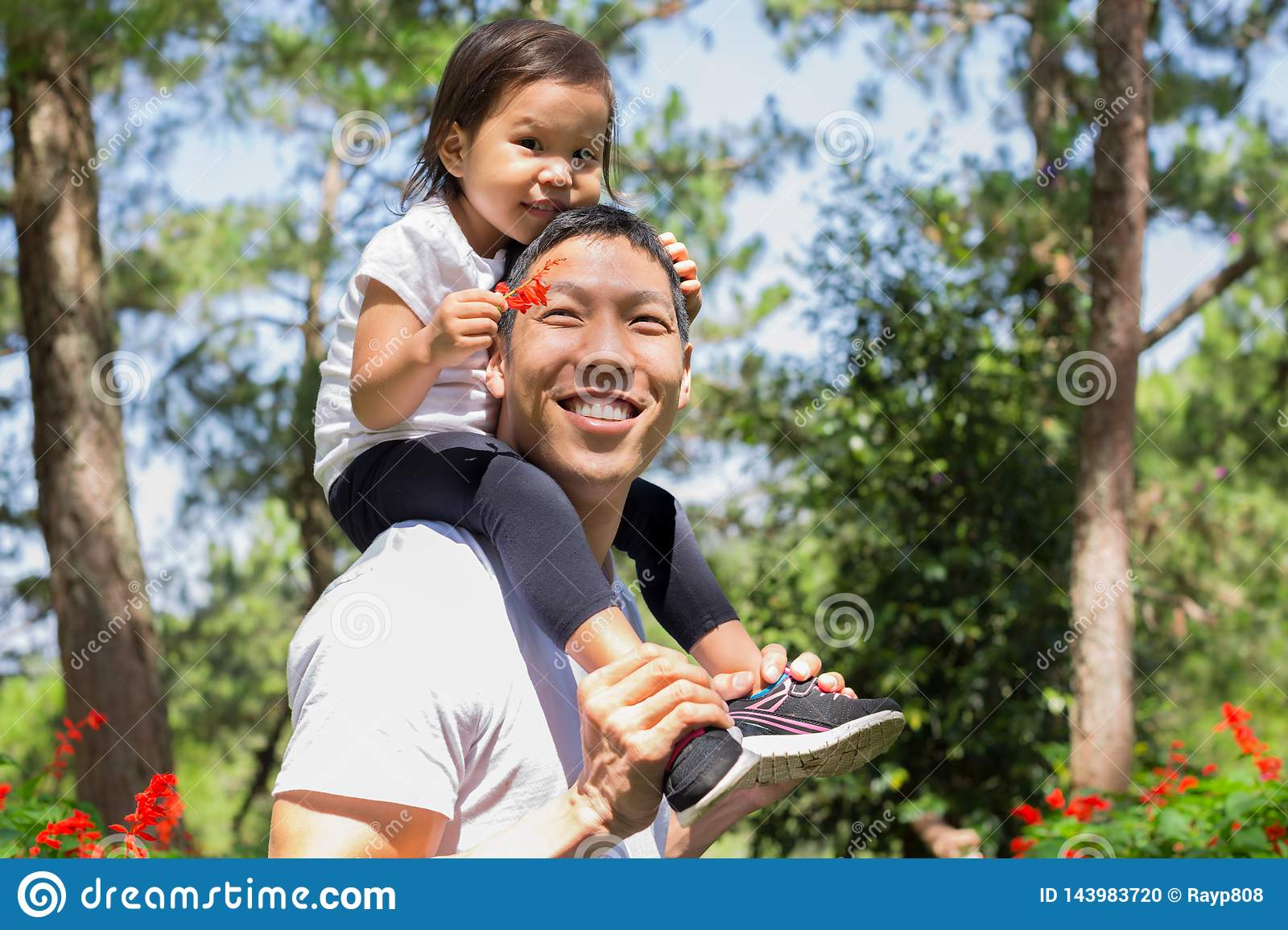 Happy father and child laughing and playing together, caring daughter on his back at a outdoor forest park