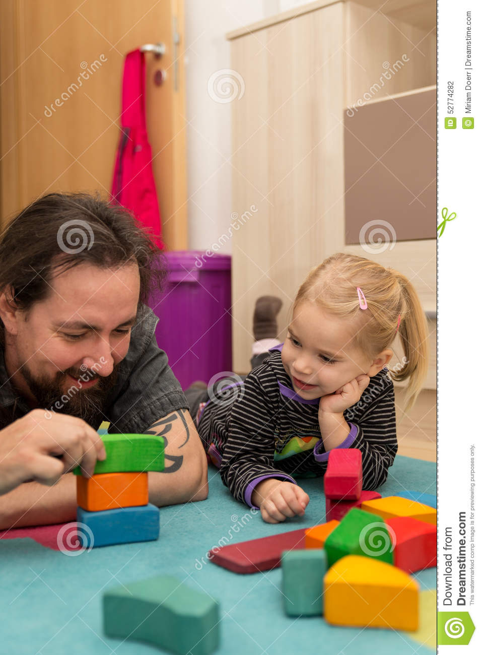 Father exhibiting bricks to his daughter