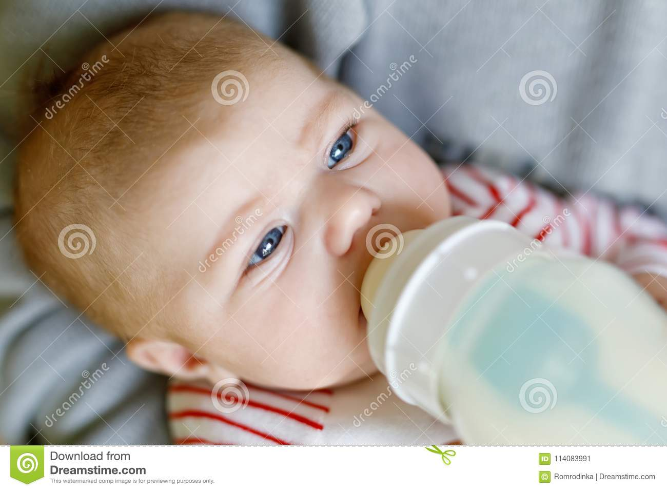 An adult drinking from a baby bottle