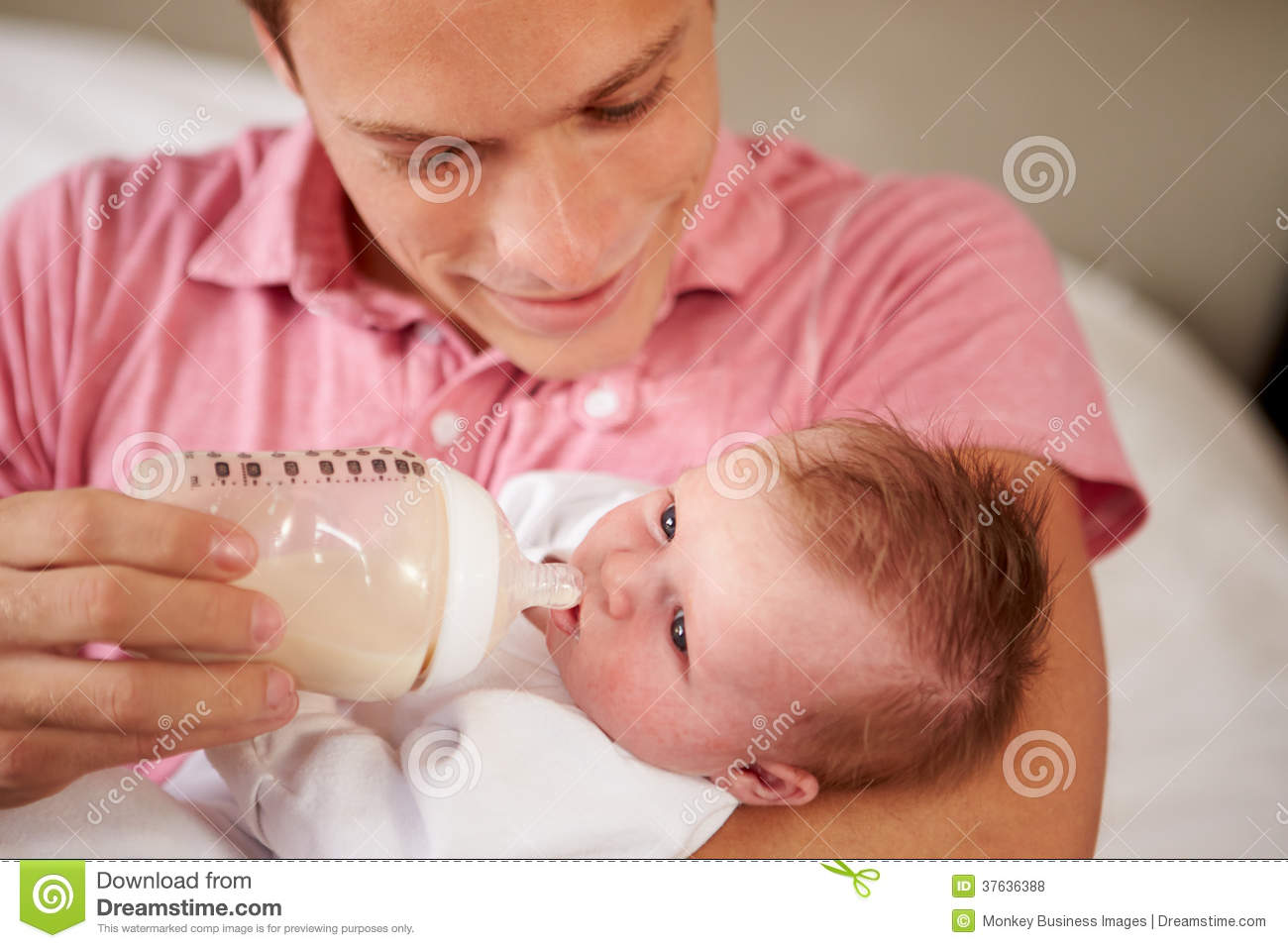 Father Giving Baby Daughter Bottle Of Milk