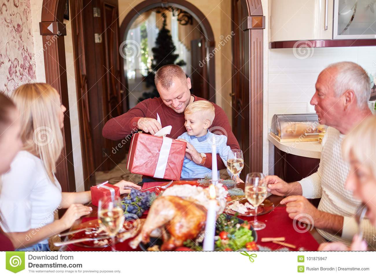 dad giving a red gift to little son on a festivebackground family christmas presents concept