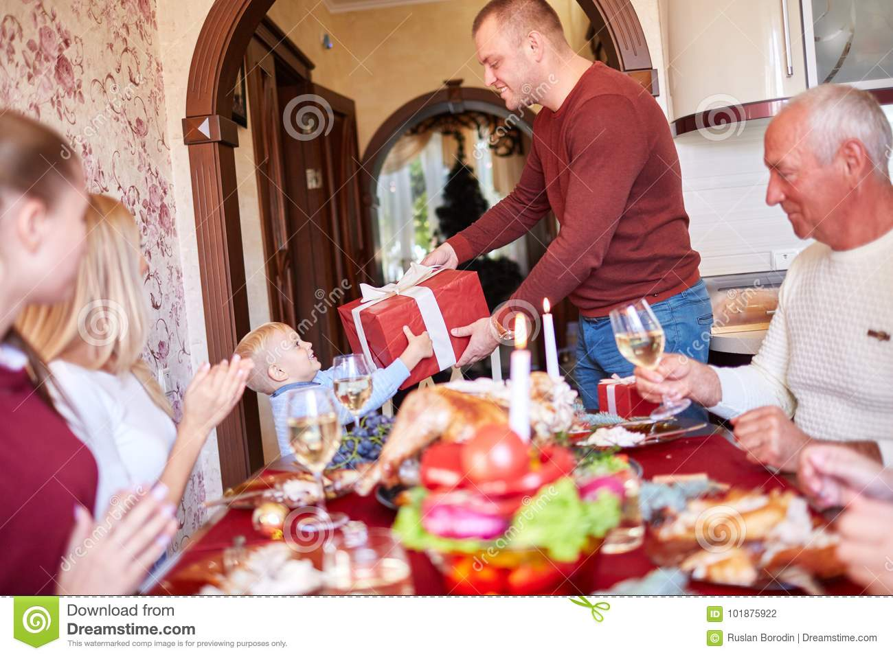 Dad giving a red gift to little son on a festivebackground. Family Christmas presents concept.
