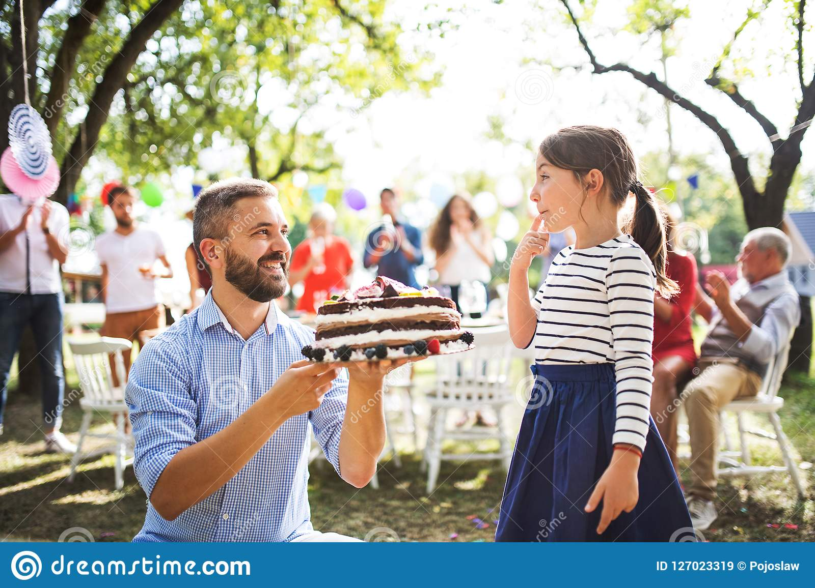 Father giving a cake to a small daughter on a family celebration or a birthday party.