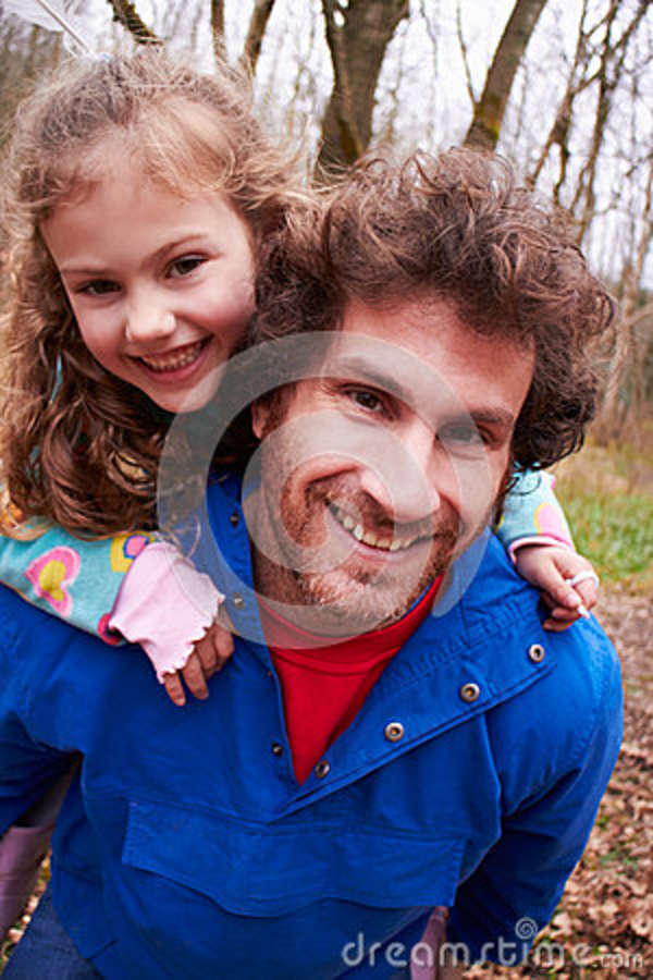 Father Giving Daughter Piggyback Ride On Countryside Walk