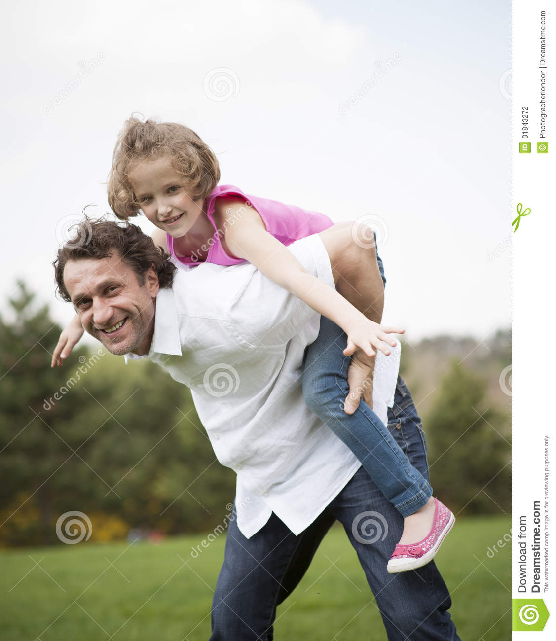 Father Giving Young Daughter Piggyback Ride Stock Photo
