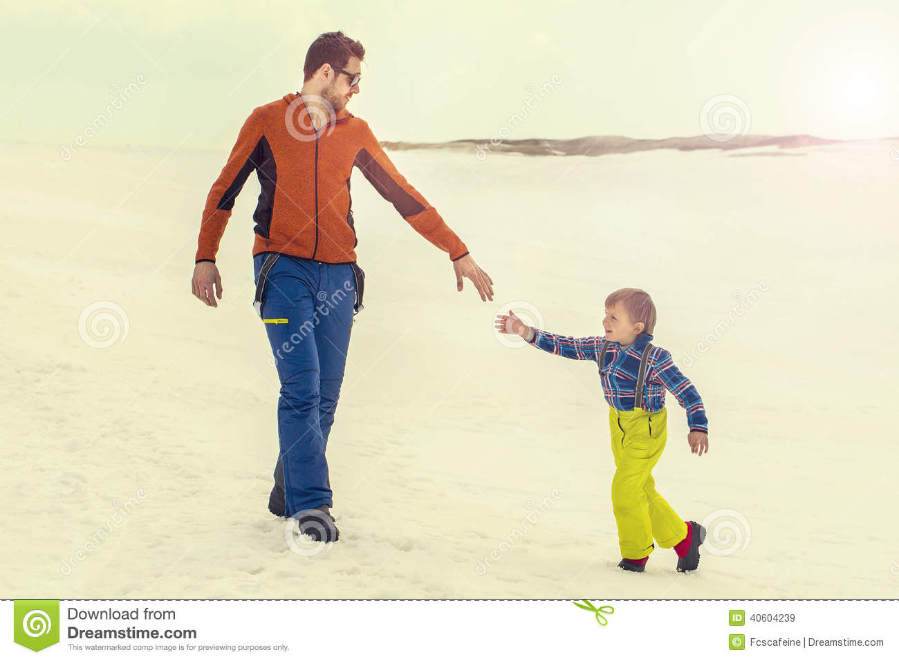 Father help his young son giving him his hand, snow