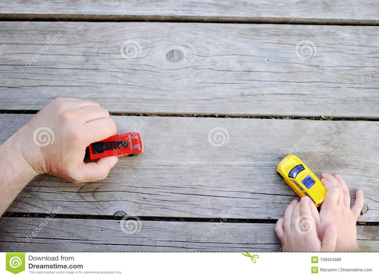 Father with his little son playing with toy cars