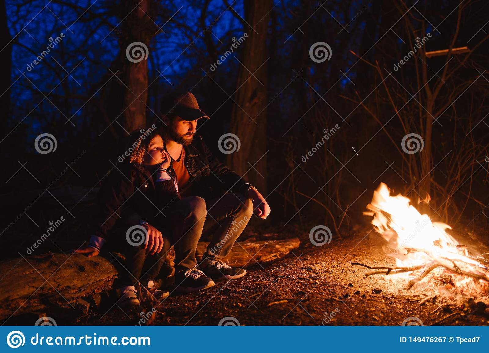 Father and his little son sitting together on the logs in front of a fire at the night. The hike in the forest.