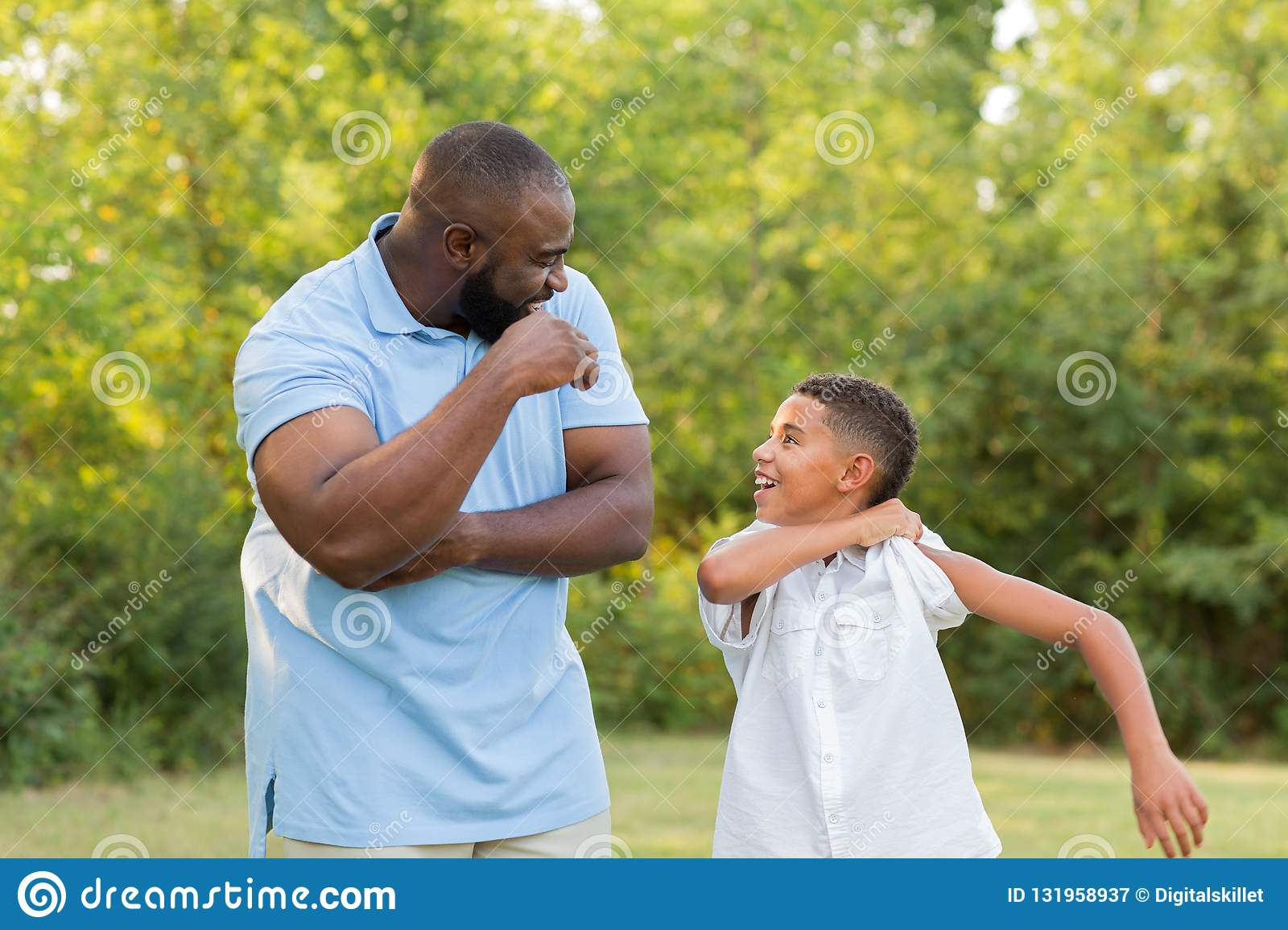 Father and his son laughing and playing at the park.