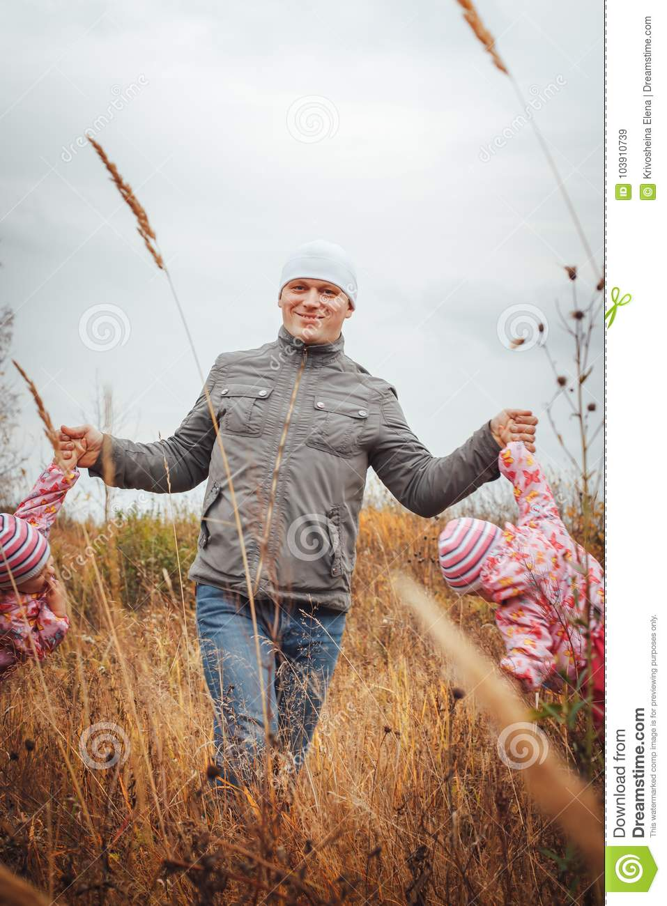 Father and his two daughters child girls have fun in the field