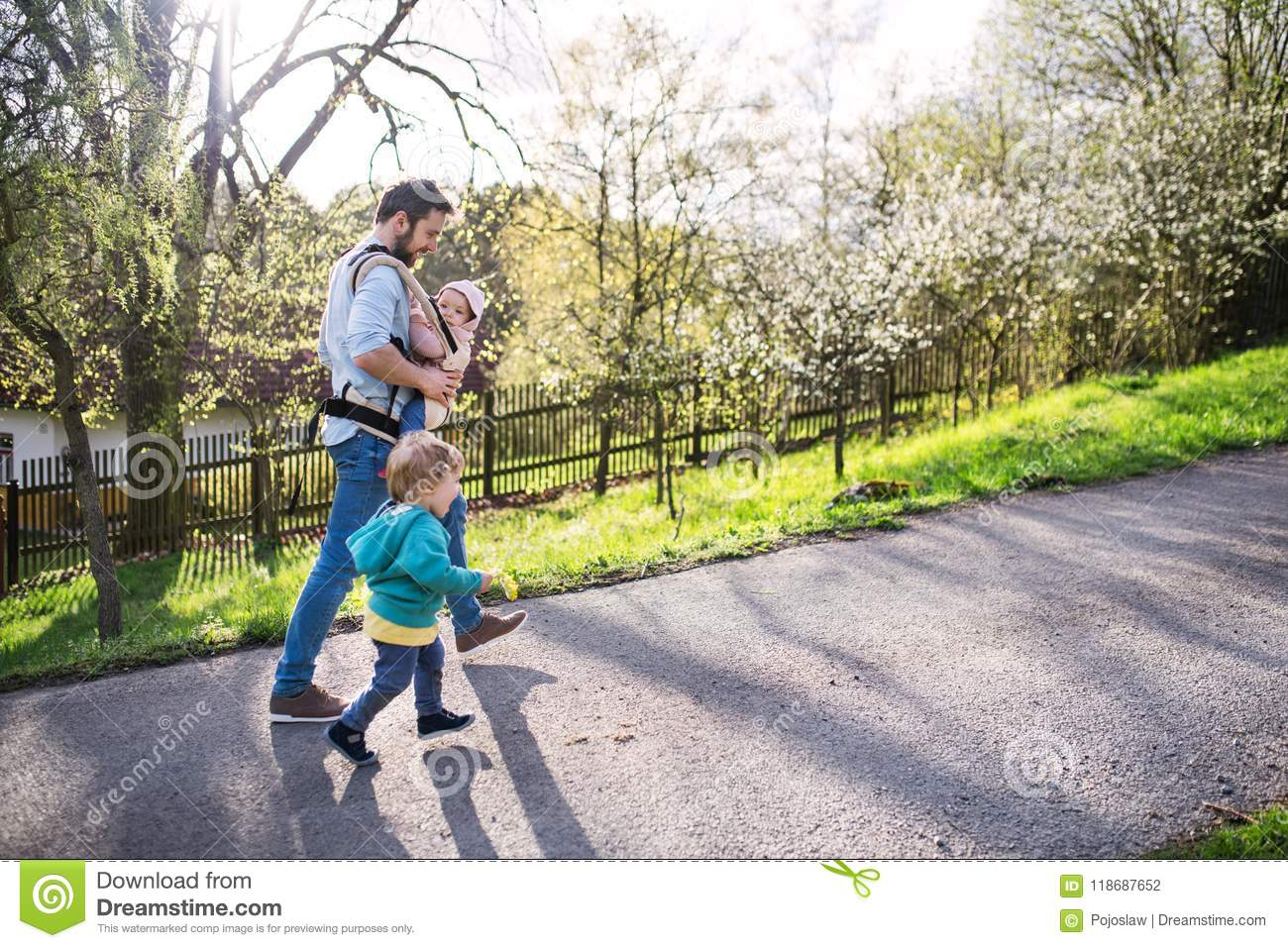 A father with his toddler children outside on a spring walk.