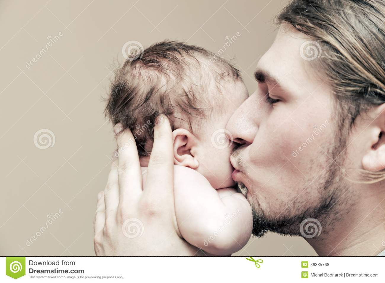 Father with his young baby cuddling and kissing him on cheek
