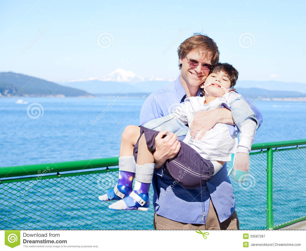 Father Holding Disabled Son In Arms On Deck Of Ferry Boat ...