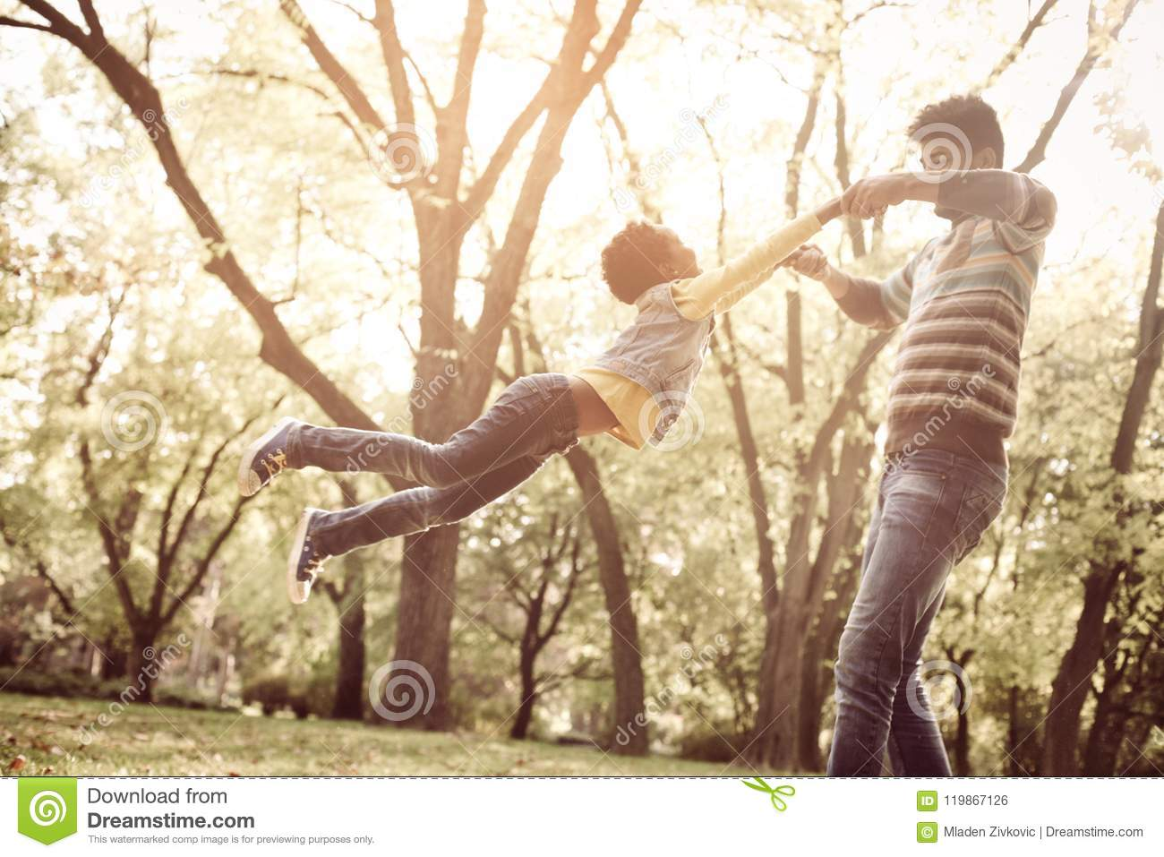 African American father holding hands of daughter and rotate in