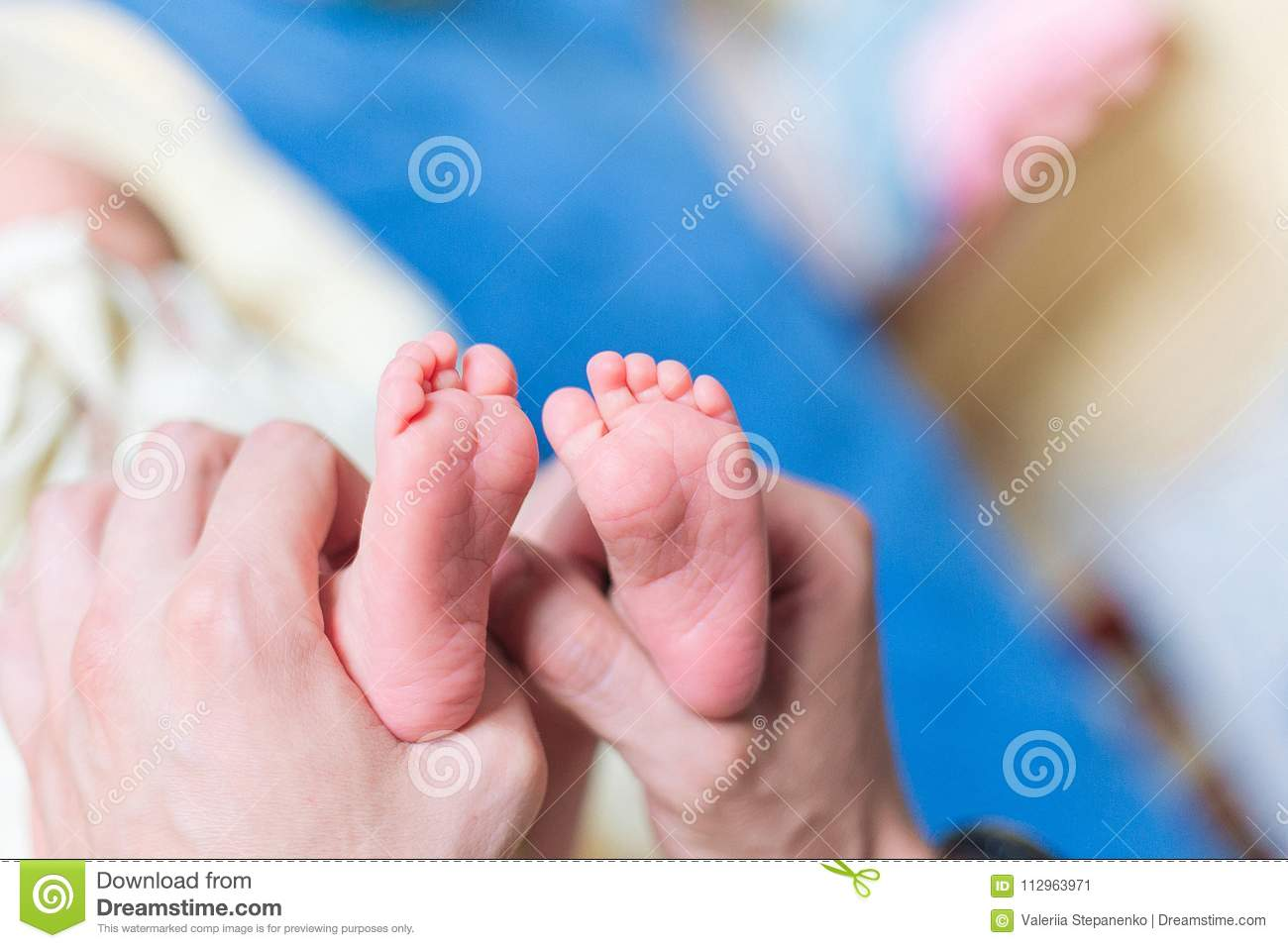 Father holding in the hands feet of newborn baby
