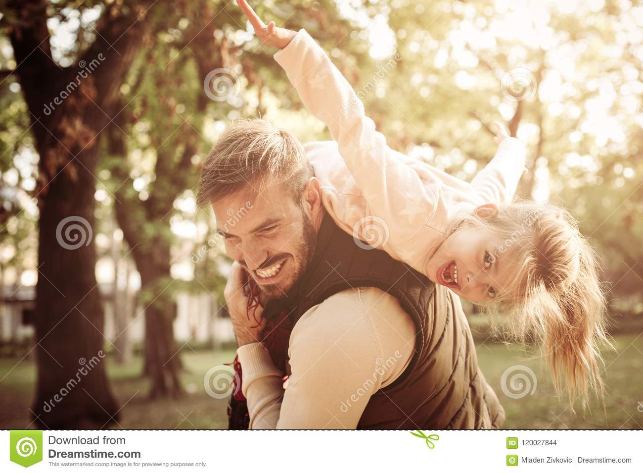 Father holding his daughter on shoulders and playing to