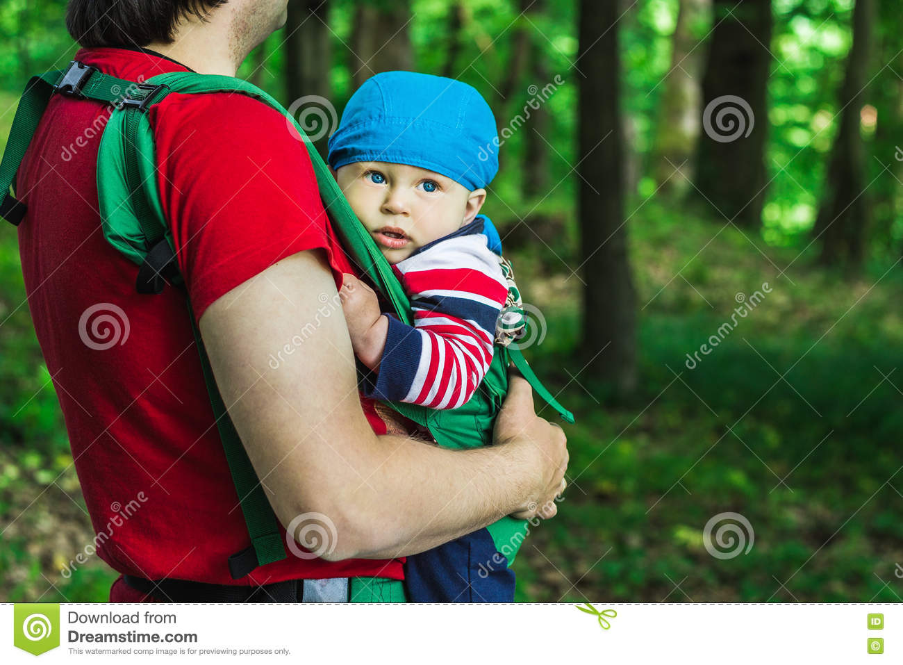 Father Holding His Son In Baby Carrier Walking In The Park Stock