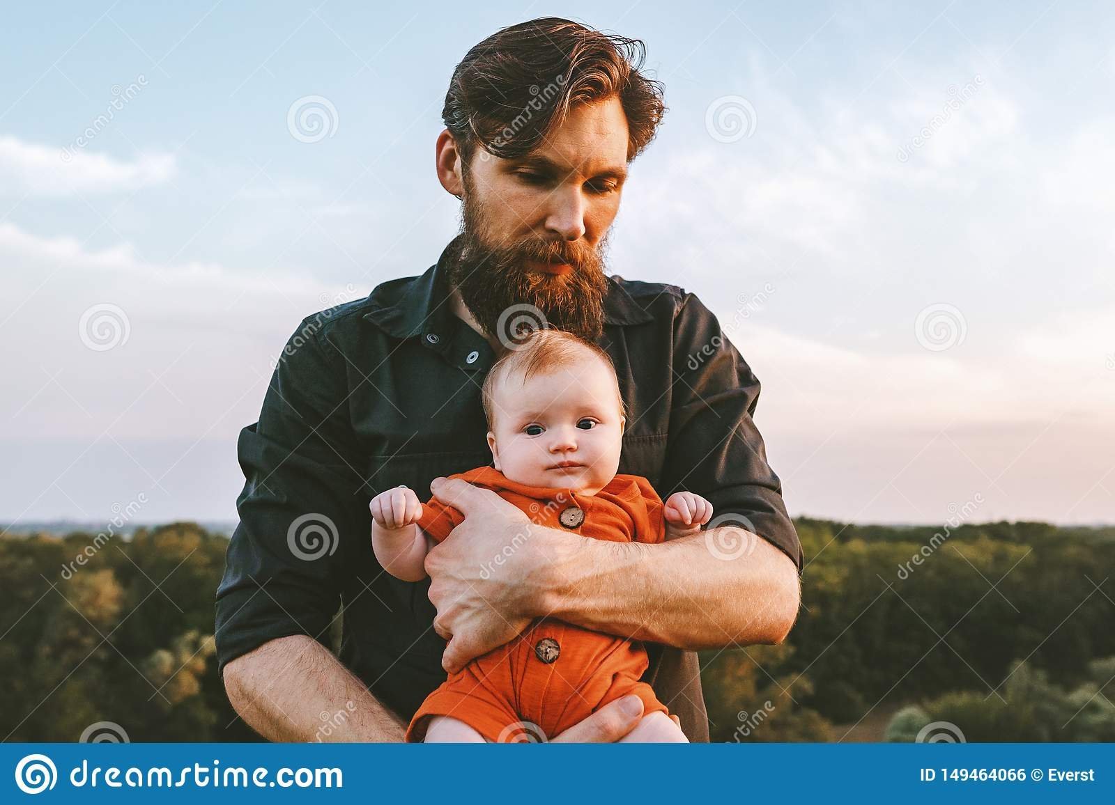 Father holding infant baby walking together outdoor