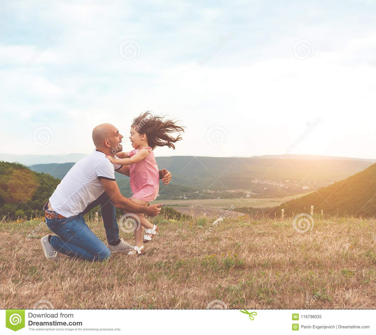 Father holds his pretty daughter and they are hug