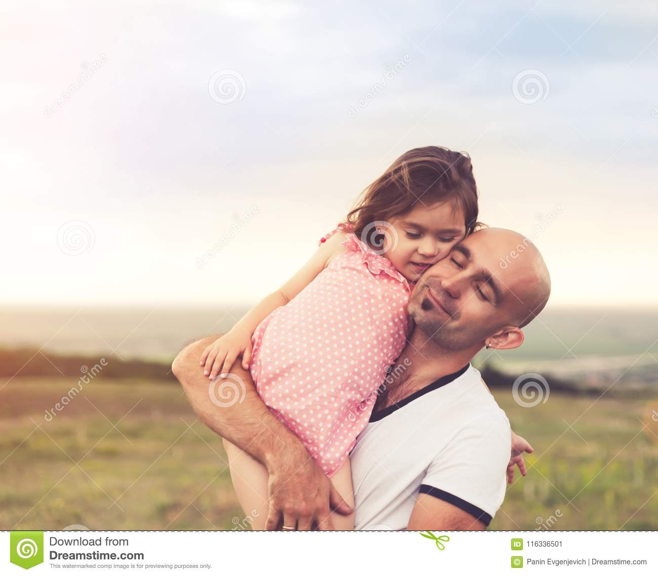 Father and daughter hugging on summer sunset