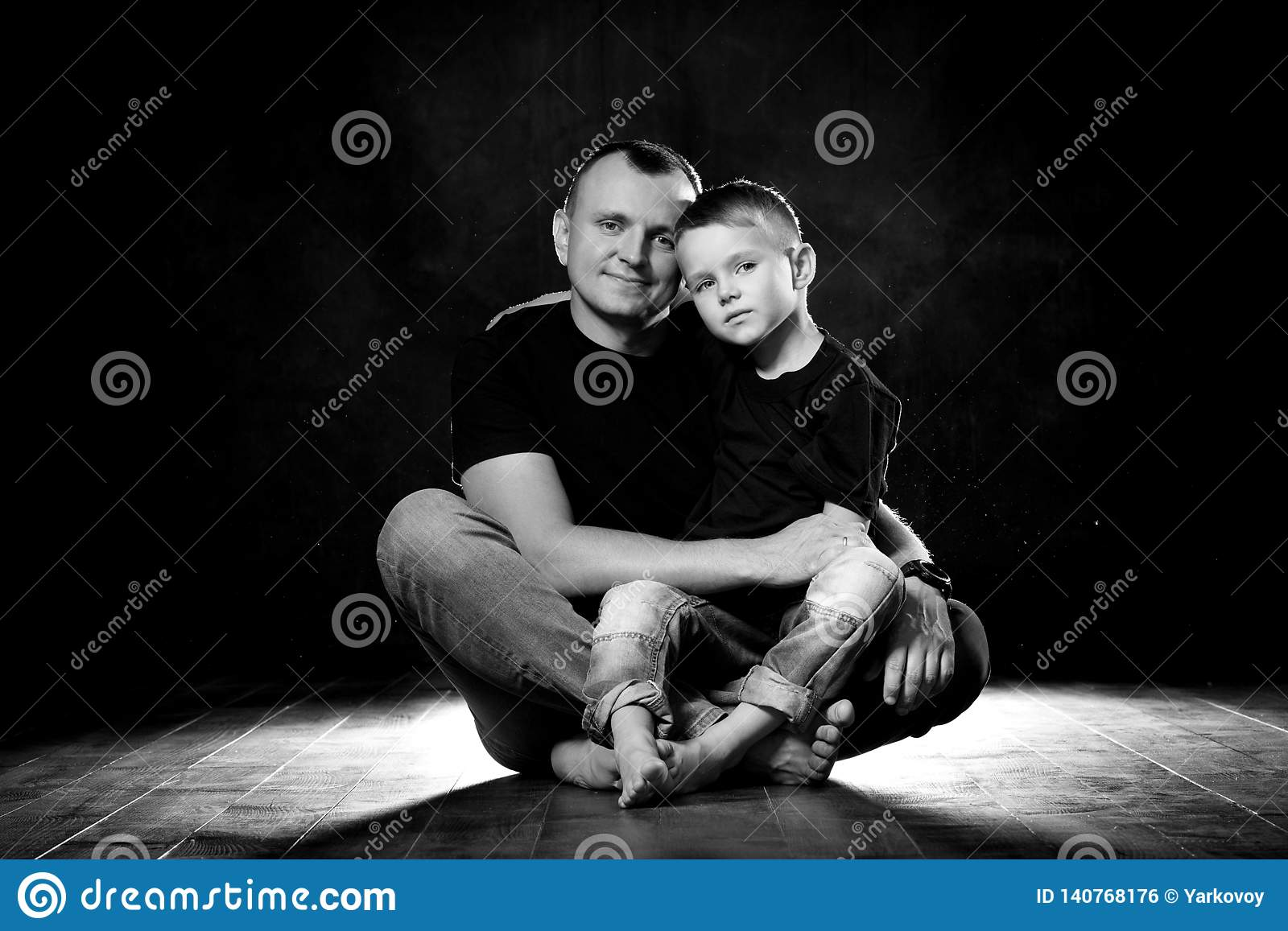Father holds son in his arms and hugs him. Man and boy are sitting together against a black background. Happy fatherhood and