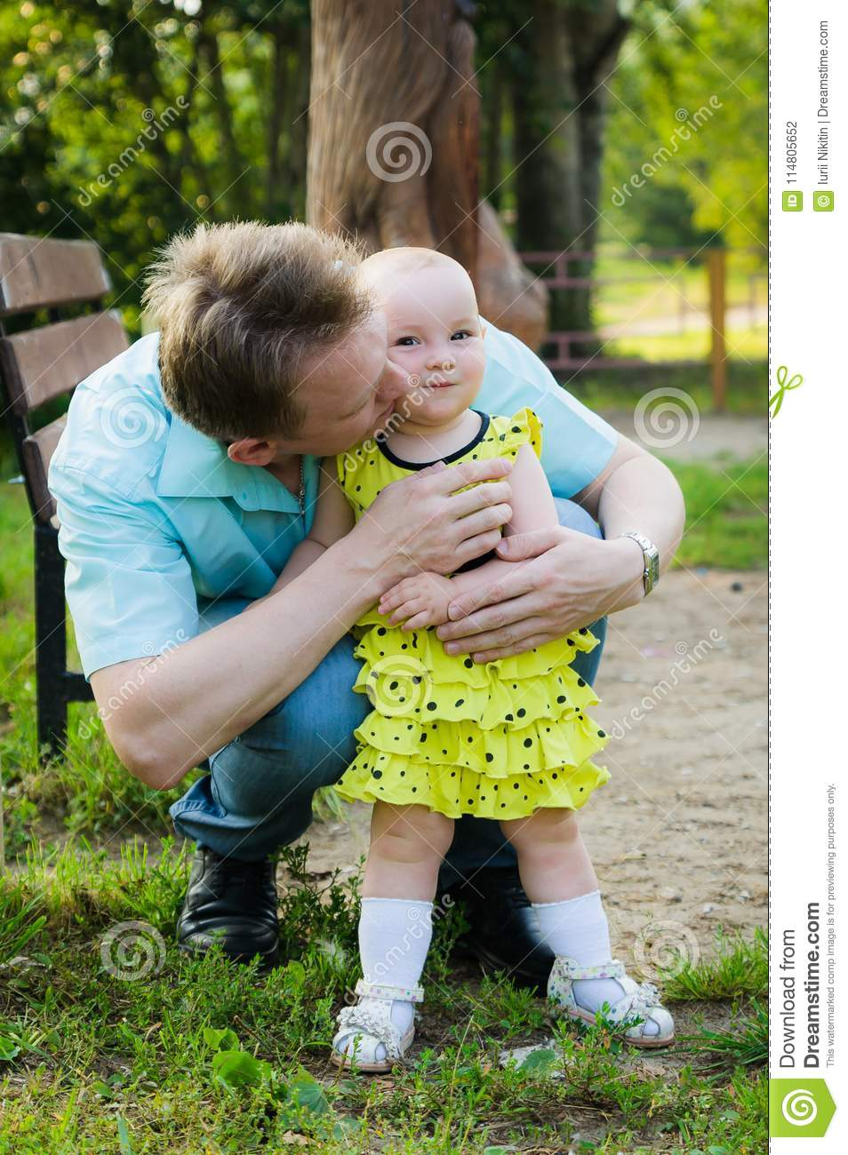 Father hugs a little daughter in a yellow dress