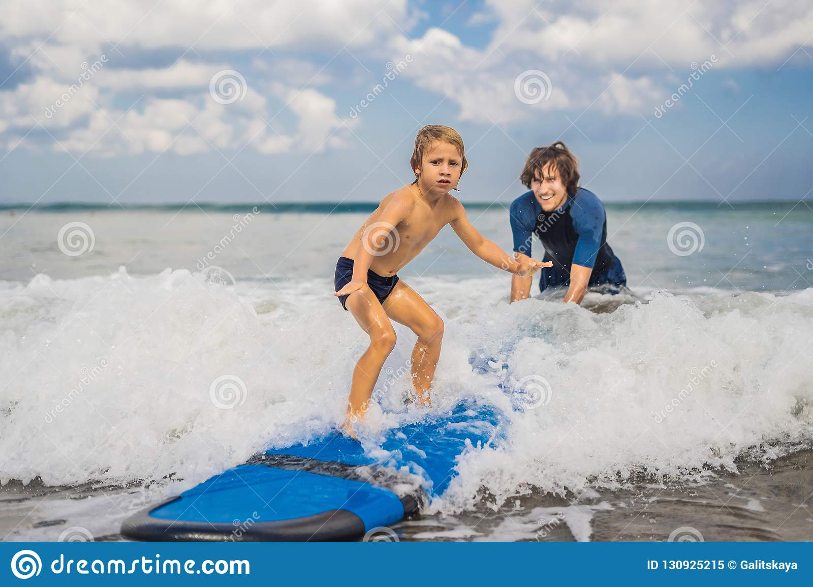 Father or instructor teaching his 4 year old son how to surf in