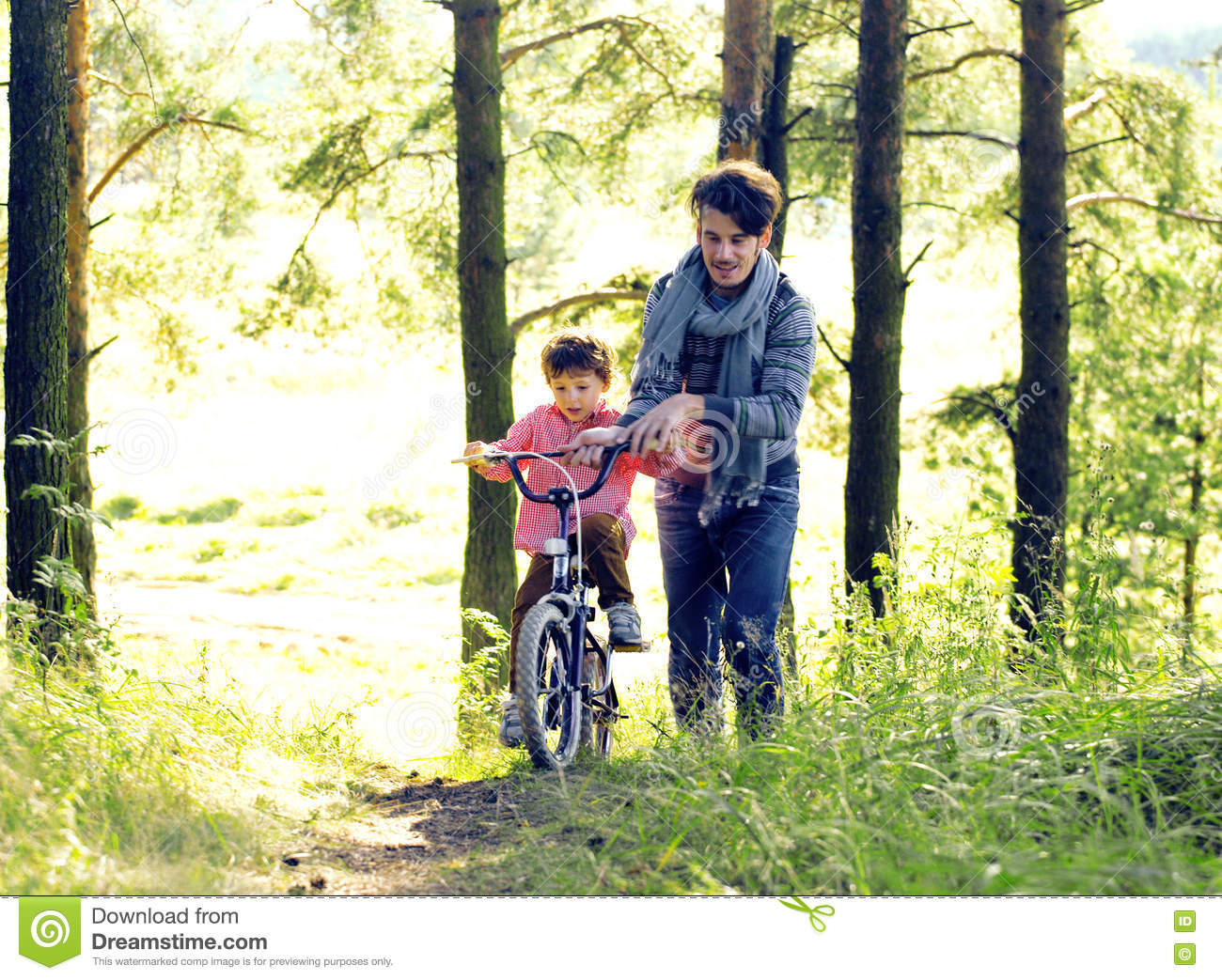 Father Learning His Son To Ride On Bicycle Outside, Real ...
