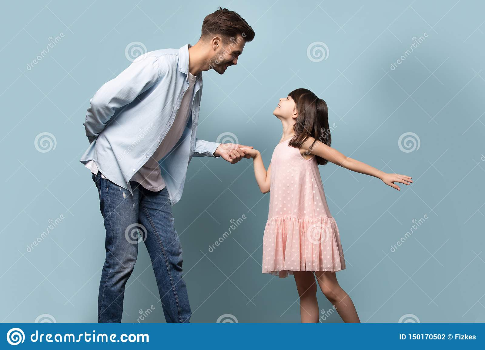 Father and little daughter holding hands dancing waltz studio shot